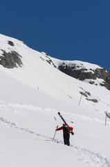 Ski patrol climbing up a mountain slope carrying large skis