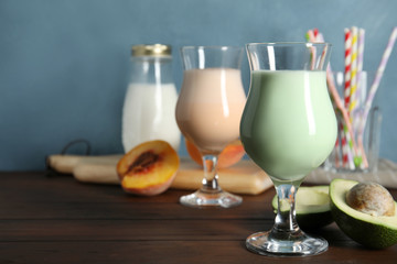 Glasses with delicious milk shakes and ingredients on table