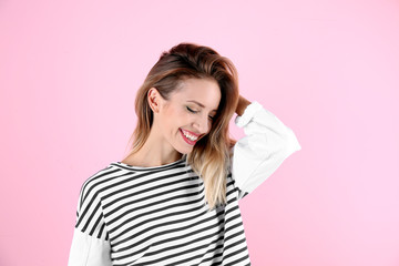 Portrait of beautiful laughing woman on color background