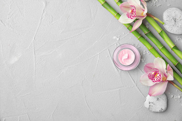 Composition with bamboo branches and flowers on light background, top view. Space for text