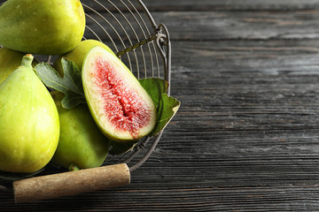 Fresh ripe figs in basket on wooden table, top view. Space for text