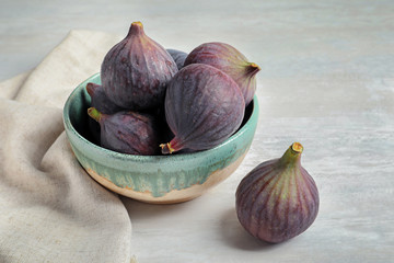 Bowl with fresh ripe figs on light background. Tropical fruit