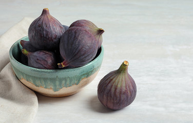 Bowl with fresh ripe figs on light background. Space for text