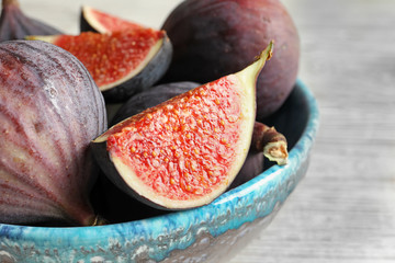 Bowl with fresh ripe figs on table, closeup. Tropical fruit