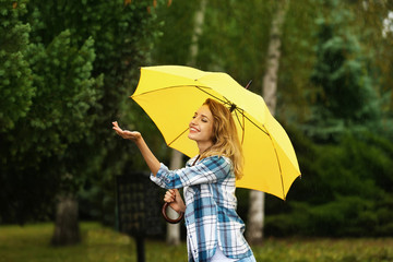 Happy young woman with umbrella under rain in park