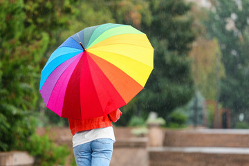 Young woman with bright umbrella under rain outdoors