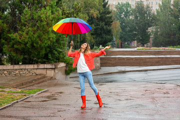 Happy young woman with bright umbrella under rain outdoors