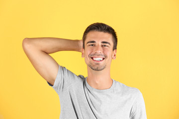 Portrait of handsome young man smiling on color background
