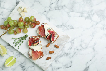 Sandwiches with ripe figs and delicious products on marble table, top view. Space for text