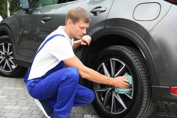 Man washing car wheel with rag outdoors