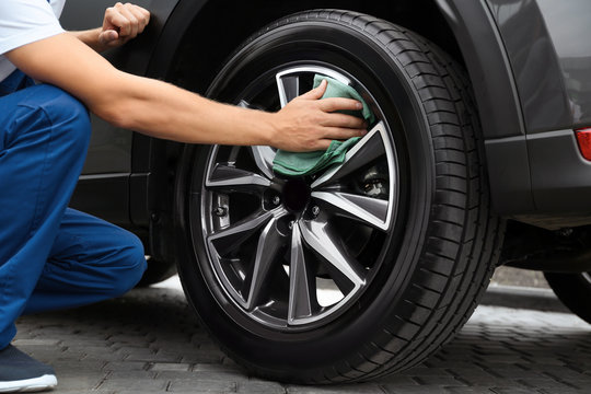 Man washing car wheel with rag, closeup