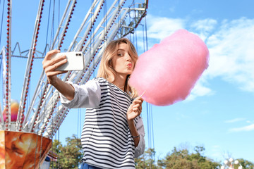 Attractive woman taking selfie with cotton candy in amusement park