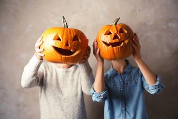 Women holding Halloween pumpkin head jack lanterns against color background