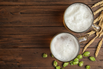Flat lay composition with tasty beer and fresh green hops on wooden background. Space for text