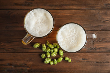 Flat lay composition with tasty beer and fresh green hops on wooden background