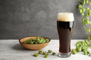 Composition with tasty beer and fresh green hops on wooden table. Space for text