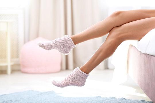 Closeup view of woman in socks sitting on bed. Floor heating