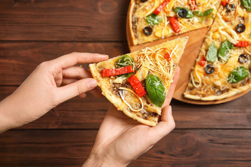 Woman holding delicious homemade pizza slice on wooden background
