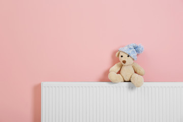 Teddy bear with knitted hat on heating radiator near color wall. Space for text
