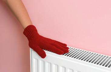 Woman in glove warming hand on heating radiator near color wall