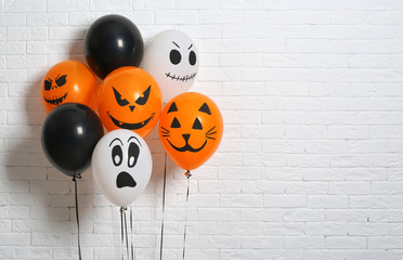Color balloons for Halloween party against white brick wall. Space for text