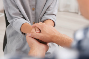 Man holding woman's hands indoors, closeup. Concept of support and help