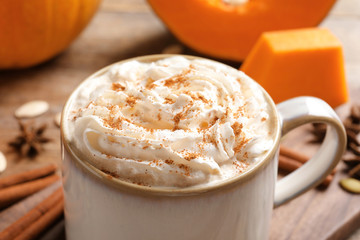 Cup with tasty pumpkin spice latte on table, closeup