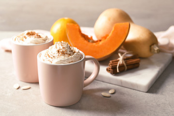 Cups with tasty pumpkin spice latte on gray table