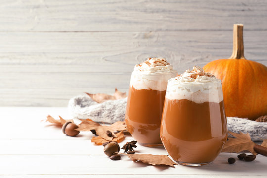 Glasses with tasty pumpkin spice latte on wooden table. Space for text