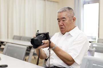 カメラを持つ高齢の男性