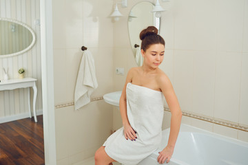 A young girl is standing in a towel by the mirror in the bathroom.