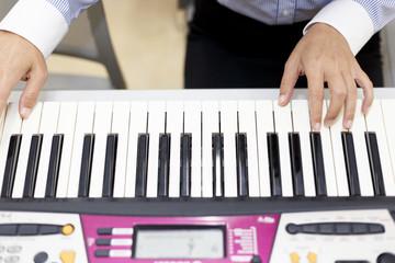 電子ピアノを弾く女性の手
