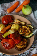 Healthy and healthy food: grilled vegetables, zucchini, eggplant, tomato, onion cooked on fire, on a dark background