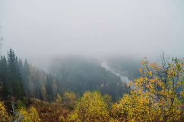Autumn landscape: fog over the forest and river, top view. The concept of traveling in the wild.