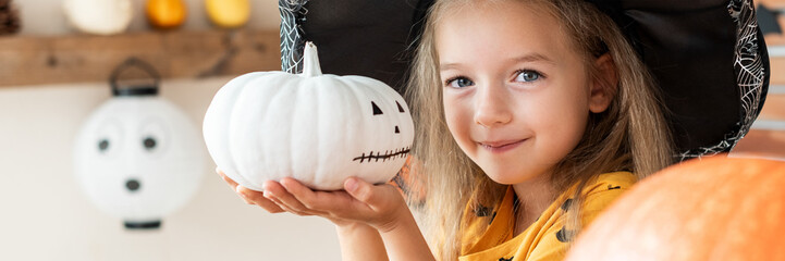 Cute little girl in witch costume holding hand painted pumpkin and smiling. Halloween holiday concept.