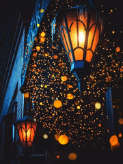 A Magical Old Street Lanterns Shines on the Street at Night. Many bright lights around. Vintage Old Street Classic Iron Lanterns On The House Wall. Christmas or Halloween Magic Fairy Lanterns
