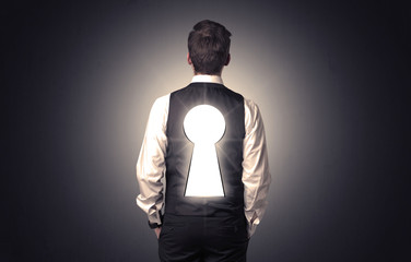 Young businessman standing and thinking with black keyhole on his back