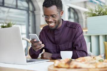 Cheerful dark skinned guy installs app on laptop computer, shares media on smart phone, uses wireless internet connection in cafeteria, searches website, drinks hot beverage, has shining smile