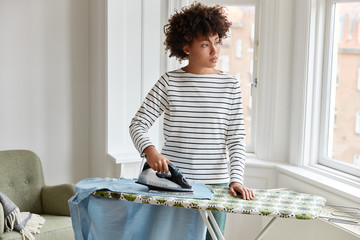 Thoughtful dark skinned young housewife in striped clothes irons clothes on ironing board, uses electric iron stands in laundry, looks out of window, being busy with housework. Household concept.