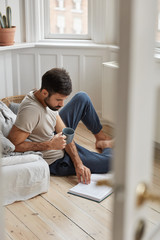 Photo of handsome guy relaxes with literature, enjoy relax at home, concentrated on reading, dressed in casual clothes, sits on floor, holds cup with coffee or tea. People and lifestyle concept