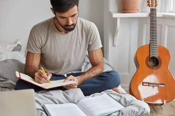 Cropped shot of serious unshaven young guy concentarted on writing something in notebook from book, sits crossed legs on bed, uses literature for preparation. Student makes home assigment indoor