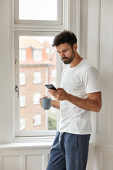 Image of handsome young Caucasian man with thick bristle, dressed in casual t shirt, uses new cellular for messaging and chatting, holds cup with coffee, stands near window, connected to wifi