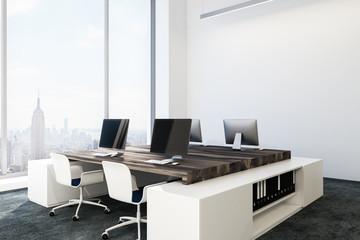 Dark wooden table in white office interior