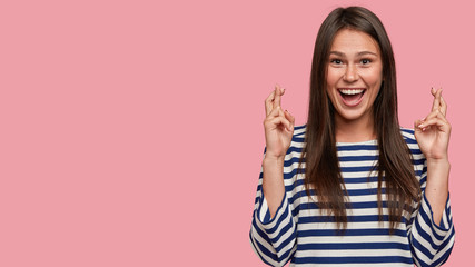 Studio shot of cheerful brunette girl has overjoyed facial expression, keeps fingers crossed, hopes for good fortune, dressed casually, isolated over pink studio wall with copy space for your text