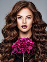 Stunning woman with long  hair and bright violet make-up.