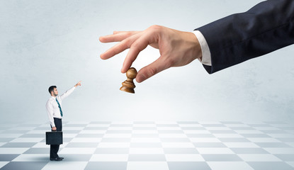Small businessman fighting against big chessman on a big hand with chess board concept