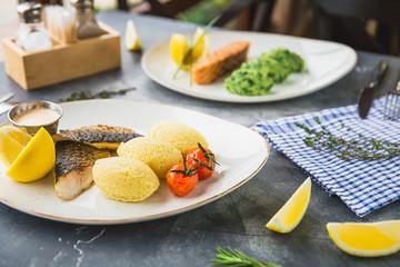 Fish dishes with millet porridge, tomato, lemon slice and shrimp sauce on table in restaurant