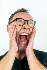 Close up portrait with white background of a adult male with grizzled beard and glasses shouting.