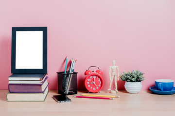 Mock up picture frame, books, office supplies, plant on desk with pink wall