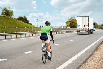 Road cyclist wearing helmet, riding a race at high speed, during a time trial contest on the highway outside the city. Man cycling road bike and exercise in sprint track. Dangerous sport concept